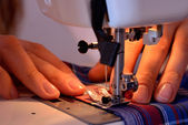 Close-up female hands sewing fabric on sewing machine — Stock Photo