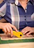 Close-up female hands cutting fabric with patchwork rotating cutter — Stock Photo