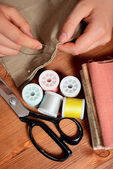 Close-up female hands sewing fabric on old wooden table — Stock Photo