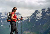 Young woman with backpack and trekking poles in mountains — Stock Photo