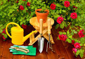 Gardening tools on wooden table and rose flowers background — ストック写真