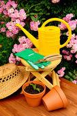 Outils de jardinage sur table en bois et fond rose fleurs — Photo