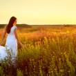 Young woman in white clothes standing in field on sunset — Stock Photo #50513433