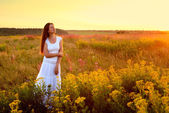 Young woman in white clothes standing in field on sunset — Foto Stock