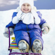 Adorable little girl on a sled at winter sunny day — Stock Photo #48633035