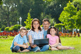 Happy Family using laptop lying on grass — Foto de Stock