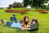 Happy Family using laptop lying on grass — Stock Photo
