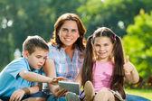 Happy Family using laptop lying on grass — Stock Photo