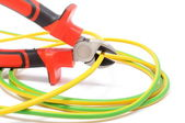 Alicate de metal e cabo verde-amarelo sobre fundo branco — Foto Stock