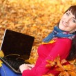 Woman with laptop in autumn park — Stock Photo #48751673