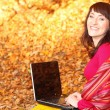 Smiling woman with laptop in autumn park — Stock Photo