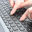 Female hand writing on a laptop keyboard — Stock Photo #48753319