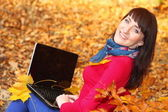 Woman with laptop in autumn park — Stockfoto