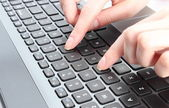 Female hand writing on a laptop keyboard — Stock Photo