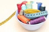 Colorful spools of thread, tape measure and thimble — Stock Photo