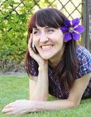 Mujer sonriente con el teléfono móvil en jardín soleado — Foto de Stock