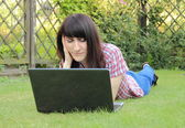 Woman with laptop in the sunny garden — Stock Photo