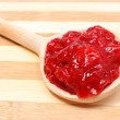 Strawberry jam with wooden spoon on cutting board — Stock Photo #48767233
