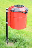 Red and wet garbage basket in a park on a background of green grass — Stock Photo