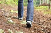 Botas de montaña y las piernas de una mujer en el camino de montaña — Foto de Stock