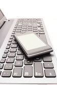 Mobile phone with laptop keyboard — Stock Photo