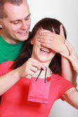 Man giving a gift to surprised smiling woman — Stock Photo
