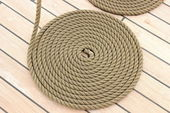 Thick rope wrapped in spiral lying on deck of ship — Stock Photo