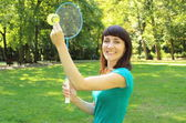 Smiling woman playing badminton in the summer park — Stock Photo