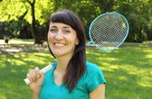 Smiling woman with badminton racket in the summer park — Stock Photo