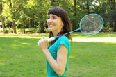 Smiling woman with badminton racket in the summer park — Foto Stock