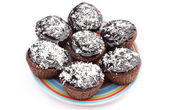 Fresh baked chocolate muffin with desiccated coconut on colorful plate — Stock Photo