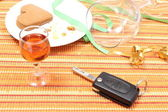 Car key with glass of wine on table after party — Stock Photo