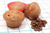 Fresh baked muffins and coffee grains on colorful cloth — Stock Photo