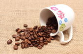 Heap of coffee grains with overturned cup — Stock Photo