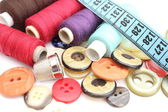 Colorful spools of thread, tape measure, thimble and buttons — Stock Photo
