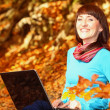 Woman with laptop in autumn park — Stock Photo
