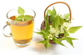 Fresh nettle in wicker basket and cup of beverage — Stock Photo