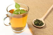 Fresh and dried nettle with cup of beverage — Stock Photo