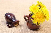 Yellow flowers of dandelion in brown vase — Stock Photo