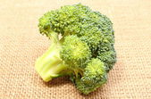 Portion of fresh green broccoli on jute canvas — Stock Photo