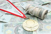Gold medal and roll of tied banknotes on money background — Stock Photo