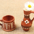White daisy in brown ceramic vase on jute canvas — Stock Photo #50422629