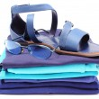 Womanly sandals and sunglasses on pile of blue clothes. White background — Stock Photo #50988067