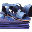 Womanly sandals and sunglasses on pile of blue clothes. White background — Stock Photo #51252871