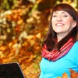 Smiling woman with laptop in autumn park — Stock Photo #51322389