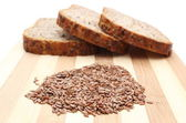 Linseed on cutting board and slices of wholemeal bread — Stock Photo