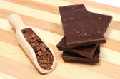 Stack of dark chocolate and grated on wooden spoon — Stock Photo