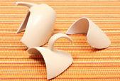 Kırık kupa, turuncu kumaş üzerine parçalanmış kupası — Stok fotoğraf