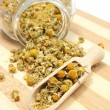 Dried chamomile in glass jar and on wooden spoon — Stock Photo #51330717
