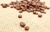 Coffee grains on jute background — Stock Photo